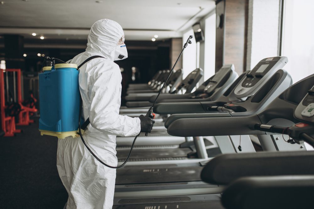 person dressed in ppe spraying disinfectant on gym equipment