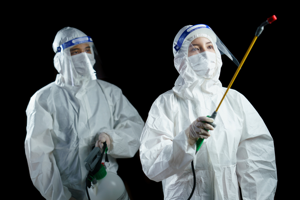 staff in ppe applying disinfectant spray to room